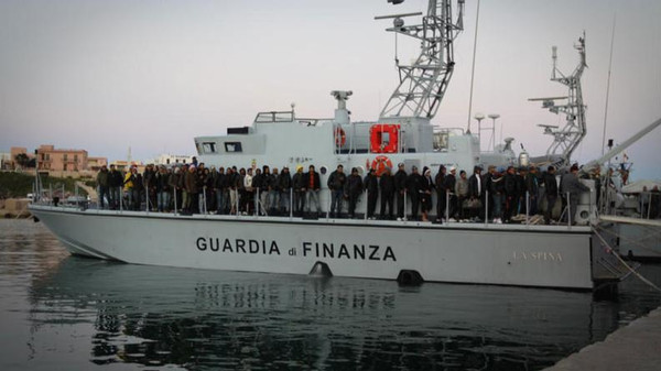 Migrants arriving from Tunisia and Libya aboard a Guardia Di Finanza boat after their own boat nearly sunk off the coast of Italy.