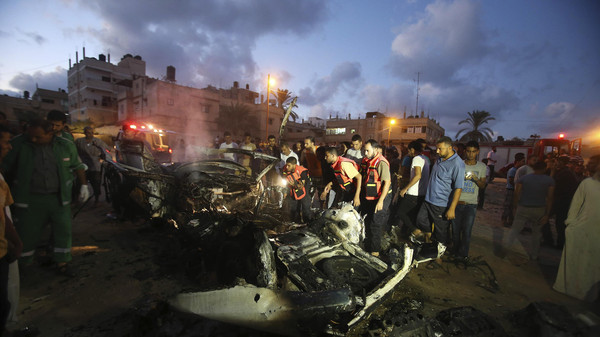Palestinian firefighters inspect a car, which witnesses said was targeted in an Israeli air strike in Rafah in the southern Gaza Strip August 9, 2014.