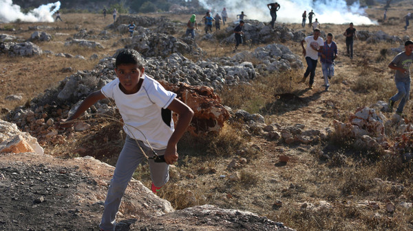 Palestinian protesters run for cover from tear gas during clashes with Israeli security forces in the West Bank.