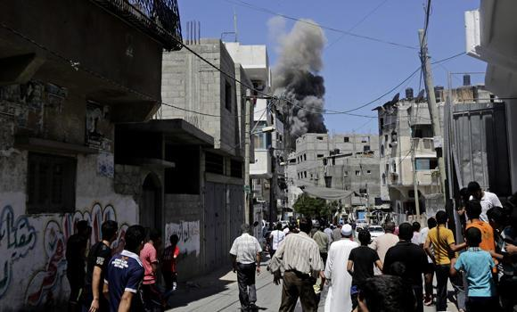 Palestinians look at smoke and dust after an Israeli strike hit Gaza City, northern Gaza Strip, on Thursday.