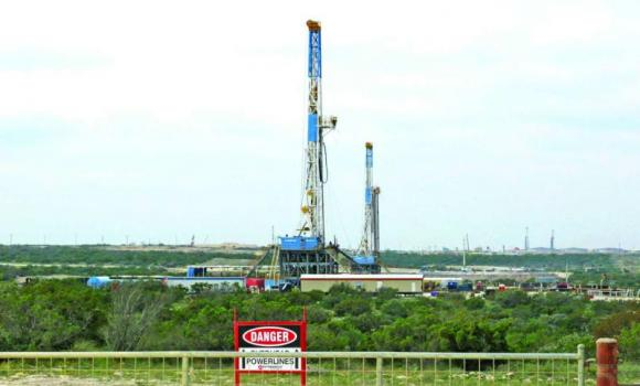 Rigs contracted by Apache Corp. drill for crude oil locked tight in shale in west Texas' Permian Basin near the town of Mertzon, Texas.