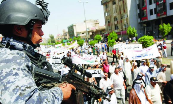 A police officer stands guard at a pro-government rally in Baghdad, on Saturday.