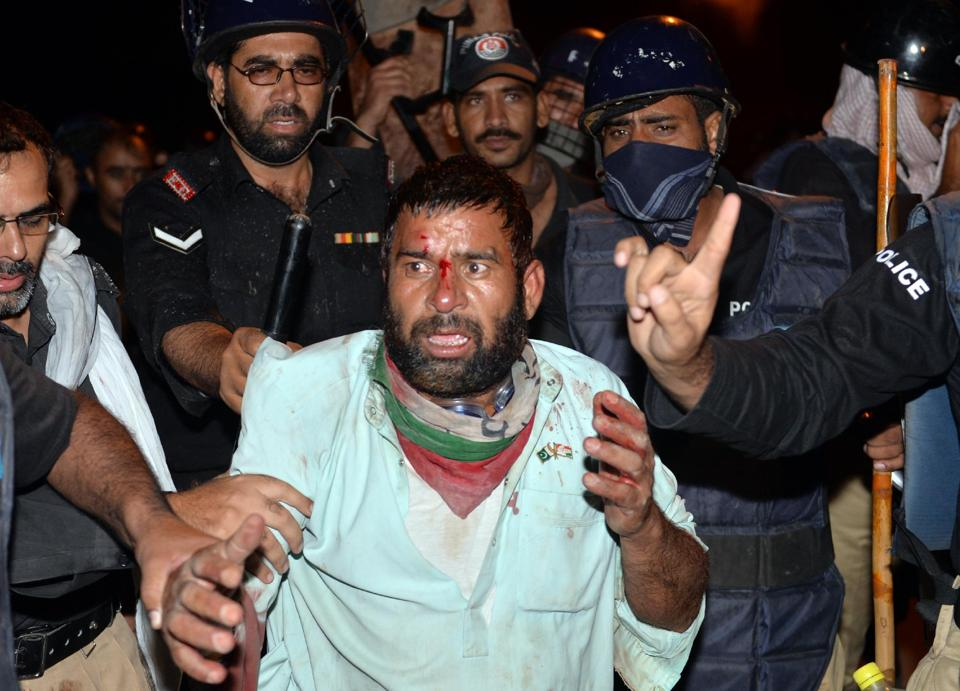 Policemen arrest an injured supporter of populist cleric Tahir-ul-Qadri in Islamabad.