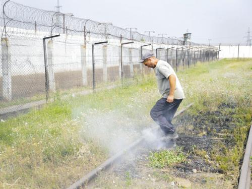 A prisoner tramples smoldering grass in a high-security facility after shelling in Donetsk, east Ukraine, on Monday