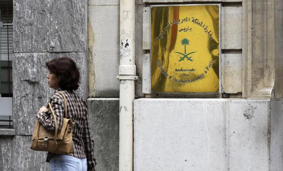 A woman walks past the entrance of the Saudi Arabian Embassy in Paris on Monday. Saudi officials in Paris say that armed robbers ambushed and stole a car rented by a Saudi man at a highway interchange on the northern edge of the French capital.