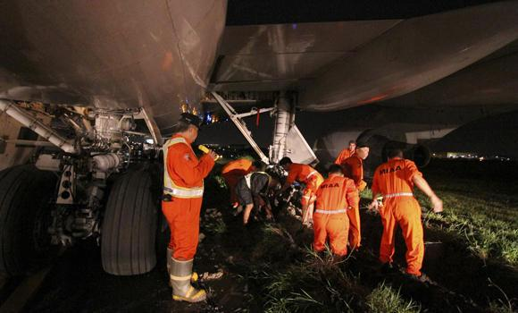 Airport crew and mechanics work to free a Saudia Airlines passenger plane which swerved off the runway and became stuck in the mud as it prepared to take off the Ninoy Aquino International Airport, at suburban Pasay city, south of Manila, late Tuesday.