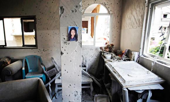 A portrait of Shahed Quishta, 8, is displayed on a concrete pillar damaged by an Israeli tank shell that slammed into the family living room on July 22, killing Shahed, in Beit Lahiya, Gaza Strip.