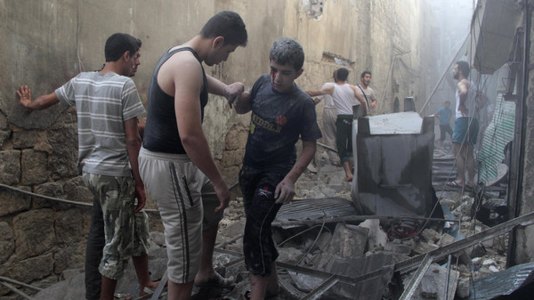 Residents help an injured boy who survived what activists said were two barrel bombs dropped at a site by forces loyal to Syria's President Bashar al-Assad in Al-Shaar neighborhood of Aleppo July 27, 2014.