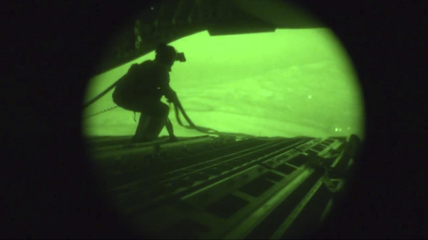 A still image captured from the U.S. Central Command night vision video footage shows an Air Force personnel retrieving straps after the U.S. military airdrop of food and water.
