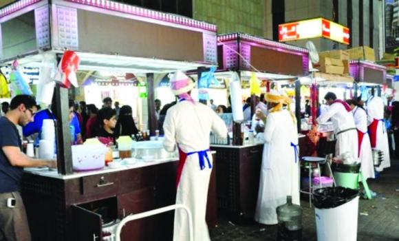 Vendors in traditional attire sell street food in Jeddah's Balad district in this Ramadan photo.