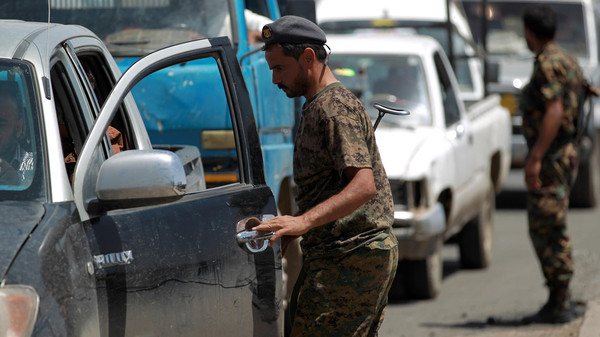 Yemeni security forces inspect a car at a checkpoint on the outskirts of the capital Sanaa. Thousands of armed Shiite rebels in Yemen strengthened their positions in the capital.