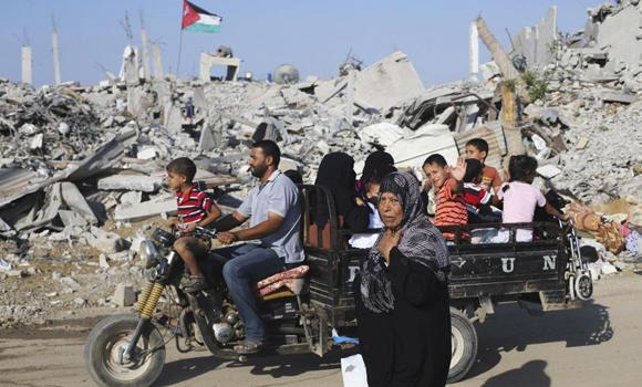 Palestinians fleeing their houses in a motorcycle rickshaw pass a house, which witnesses said was destroyed during the ongoing Israeli offensive, in the east of Khan Younis in the southern Gaza Strip, on Tuesday. Israel said Palestinian militants fired rockets from Gaza on Tuesday in violation of a truce, attacks that swiftly drew air strikes and the recall of Israeli negotiators from talks in Cairo on a long-term ceasefire.