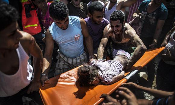 Palestinians remove the body of an eight-year-old from the rubble from a house hit by an Israeli airstrike in the al-Shati refugee camp in Gaza City on Monday. The eight-year-old girl was killed and 30 people wounded in a strike on the beachfront Shati refugee camp in Gaza City just minutes into an Israeli-declared truce, medics said.