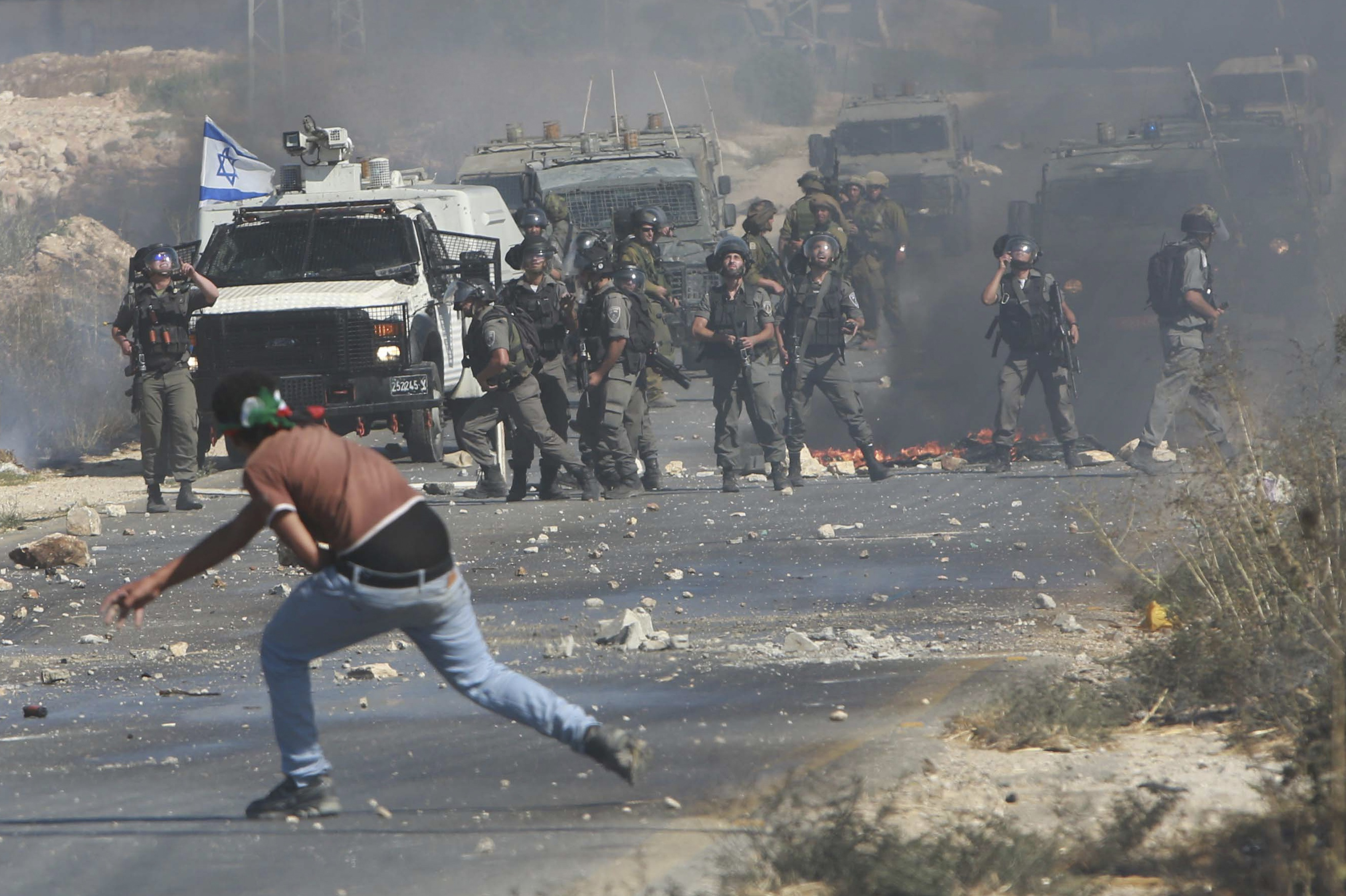 A Palestinian protester throws stones toward Israeli troops during clashes following a demonstration against the Israeli offensive in Gaza, at the Beit Fourik checkpoint near the West Bank of Nablus August 8, 2014.