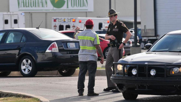 An Oklahoma State Trooper helps secure the scene at Vaughan Foods following the gruesome event.