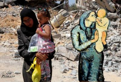 This image by Palestinian artist Basel al-Maqosui, shows a collaboration of a famous painting by Spanish painter, Pablo Picasso, paired with a photograph taken by al-Maqosui of a woman carrying her child as she walks past damages after an Israeli Strike hit the Gaza Strip.