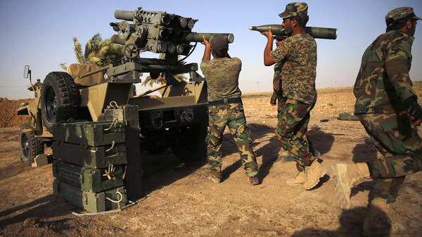 Fighters from Mahdi Army load rockets into a rocket launcher during heavy fighting with ISIS militants at Bo Hassan village in near Tikrit, northern Iraq September 12, 2014.