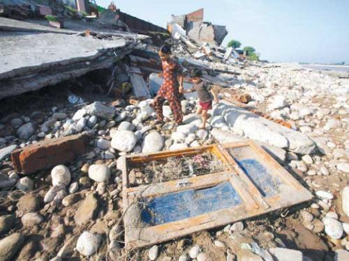 Flood affected children walk amidst the debris of a residential house which was damaged by floods on the banks of the river Tawi in Jammu on Monday.