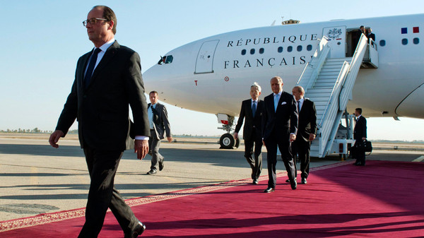 French President Francois Hollande (L) and French Foreign minister Laurent Fabius (C) exit their plane after landing at Baghdad airport September 12, 2014.