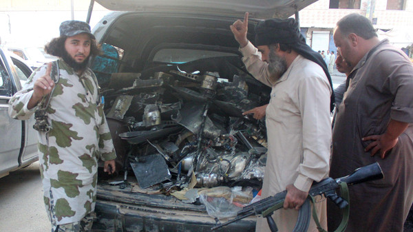 ISIS fighters gesture as they load a van with parts that they said was a U.S. drone that crashed into a communications tower in Raqqa, Syria, early on Sept. 23, 2014.