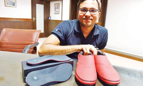CEO of Ducere Technologies, Krispian Lawrence poses with the inner soles, left, and a pair of GPS-enabled smart sports shoes, to be marketed under the name 'LeChal' in Hyderabad.