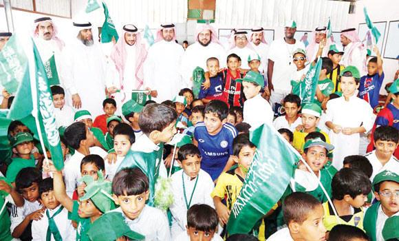 Teachers join students to celebrate the National Day at a school in Madinah as children, below, select flags in Jazan for the big day. (SPA)