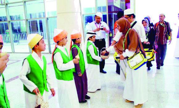 Schoolchildren welcome pilgrims with roses and Zamzam water at the Madinah airport. (SPA)