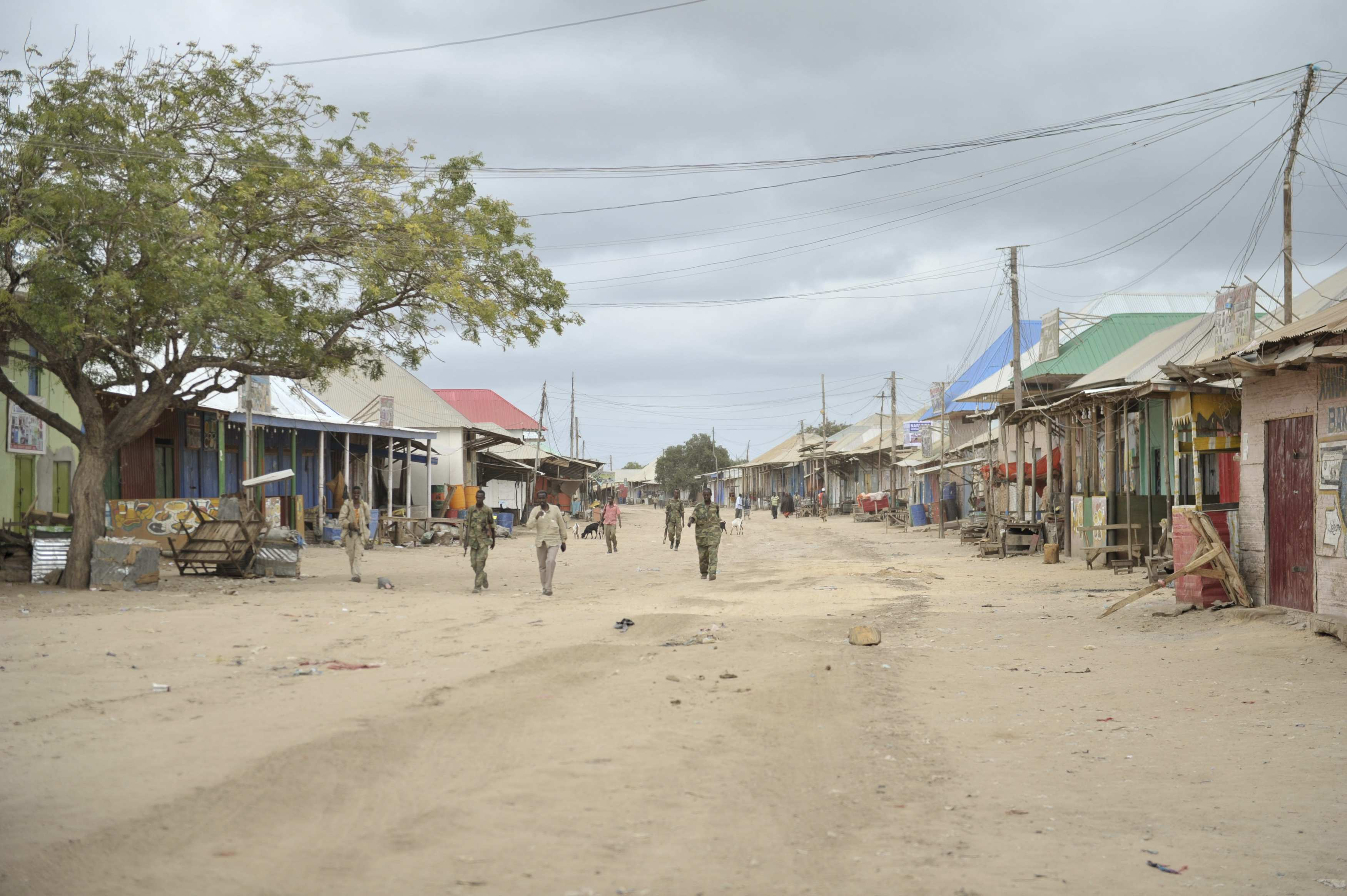 Somali soldiers and civilians walk along a street in Bulamareer, a town in the Lower Shabelle region of Somalia that was recaptured from al-Shabaab rebels.