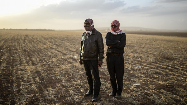 Syrian Kurdish men stand near the Syrian border at Suruc in Sanliurfa province, on Sept. 25, 2014.