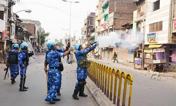A Rapid Action Force (RAF) member fires a tear gas shell to disperse a mob after clashes in Vadodara in the western Indian state of Gujarat on Sept. 26, 2014. Authorities in India's Gujarat state arrested at least 40 people after late-night clashes between Hindus and Muslims in the city of Vadodara and suspended mobile phone Internet and bulk text messaging services for four days, officials said on Sunday.