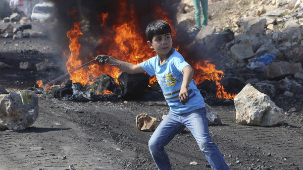A Palestinian boy uses a sling to throw stones towards Israeli soldiers during clashes following a protest against the near-by Jewish settlement of Qadomem, in the West Bank village of Kofr Qadom near Nablus October 24, 2014.