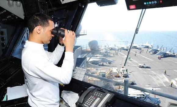 A US Navy official observes flight operations from the flight control aboard the aircraft carrier USS George H.W. Bush in the Gulf.