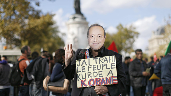 A member of the Kurdish community in France wears a mask of French President Francois Hollande during a demonstration to protest against ISIS and to bring attention to the plight of Kurds in the Syrian town of Kobani, during a march in Paris.