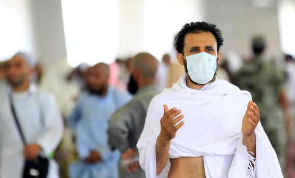 A pilgrim wears a face mask as he supplicates at the Jamarat in Mina.