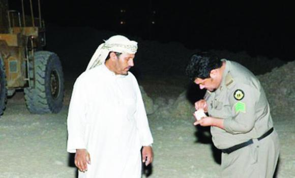 A police officer checks the papers of a foreign worker in Riyadh.