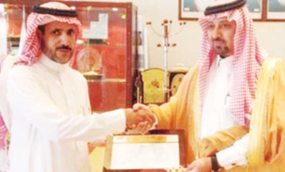 Al-Kharj Mayor Shebaili Al-Gerani handing over an agro-tourism membership license to a farmer.