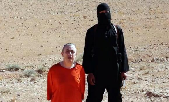 An image grab taken from a video released by the Islamic State (IS) purportedly shows a masked militant (R) before the execution of British hostage Alan Henning dressed in orange and on his knees in a desert landscape.