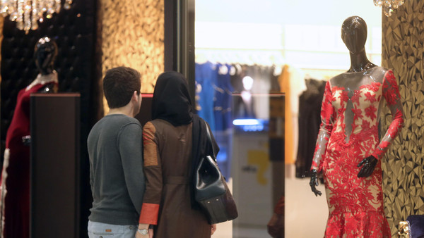 An Iranian couple look at a window display of a shop selling women's clothes at the Laleh Park shopping center in Tabriz in Iran's northwestern East-Azerbaijan province on Oct. 15, 2014.