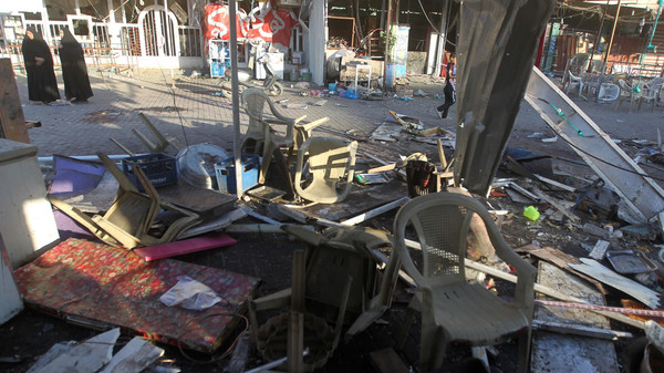 Iraqis stand at the site of an explosion in the aftermath of a car bomb attack in the mostly Shiite Sadr City district of Baghdad on October 9, 2014.