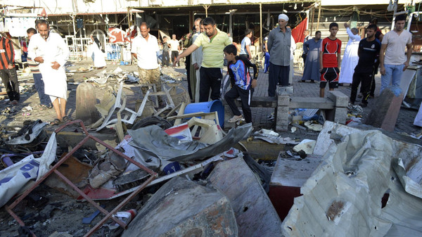 People gather at the site of Wednesday's car bomb attack in Baghdad's Sadr City October 9, 2014.