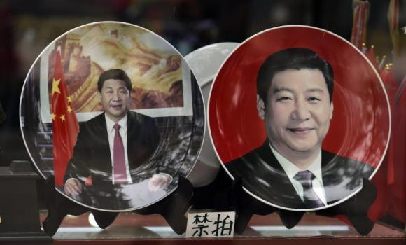Decorative plates featuring Chinese President Xi Jinping are seen in a shop window in Beijing.