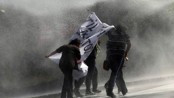 Demonstrators hold a banner as as they are sprayed by a water cannon during clashes with riot police outside of the Middle Eastern Technical University (METU) in Ankara on Oct. 9.