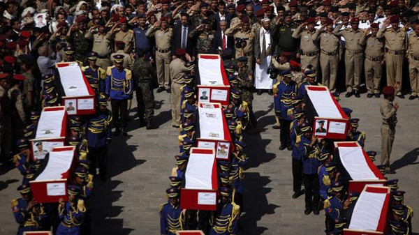 Honor guards carry the coffins of soldiers and policemen killed in attacks during a funeral procession in Sanaa.