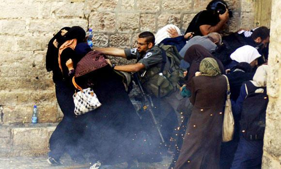 Israeli border policeman push Palestinian women during clashes in the Old City of Jerusalem, in this Oct. 13, 2014 photo. Israeli police clashed with young Palestinian protesters demonstrating against Jews visiting the Al-Aqsa Mosque compound, Islam's third holiest site, a spokeswoman said.