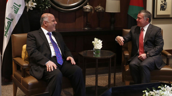 Jordan's King Abdullah (R) laughs with Iraq's Prime Minister Haider al-Abadi during their meeting at the Royal Palace in Amman October 26, 2014.