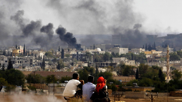 Kurdish refugees from Kobani watch as thick smoke covers the Syrian town of Kobane, October 26, 2014.