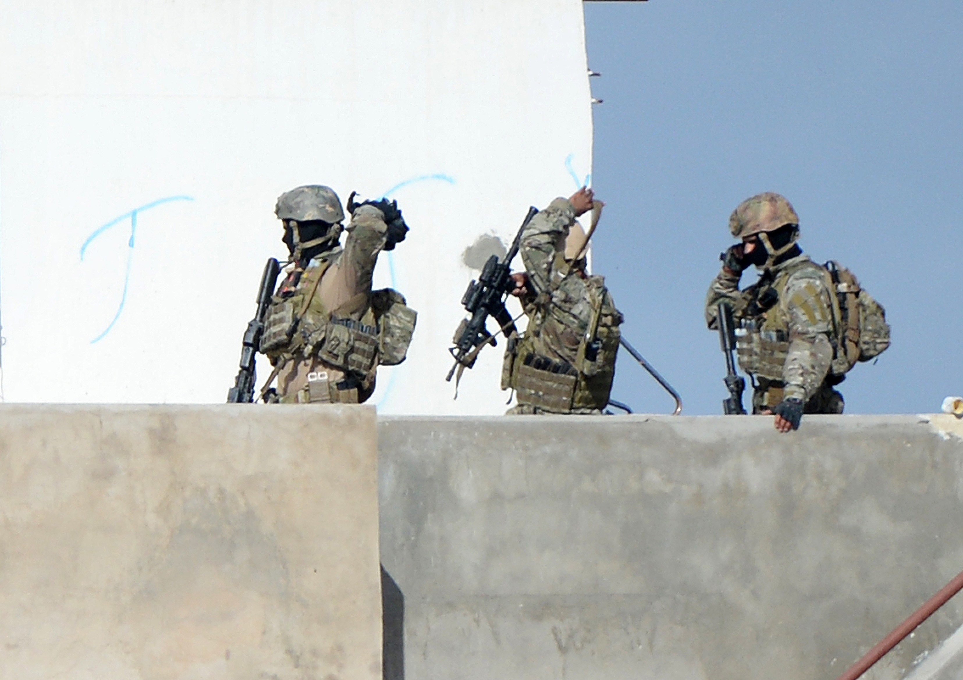 Members of the Tunisian military walk on a balcony during an operation against gunmen in the town of Oued Ellil near the Tunisian capital Tunis on Oct. 24, 2014.