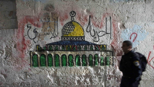 An Israeli police officer walks past a mural of the Dome of the Rock near the entrance to the compound known to Muslims as Noble Sanctuary and to Jews as Temple Mount, in Jerusalem's Old City.