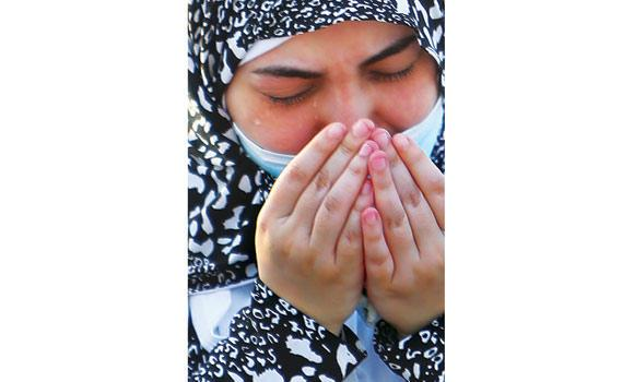 With tears streaming down her cheeks, a pilgrim seeks Allah's mercy.