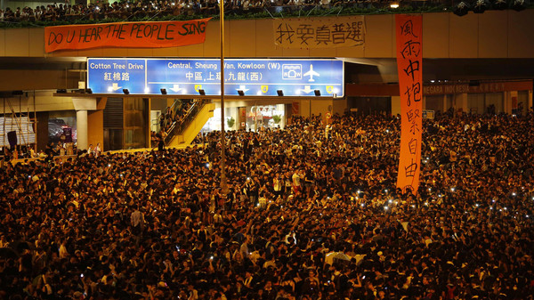 Protesters block the main street to the financial Central district, outside the government headquarters, in Hong Kong.